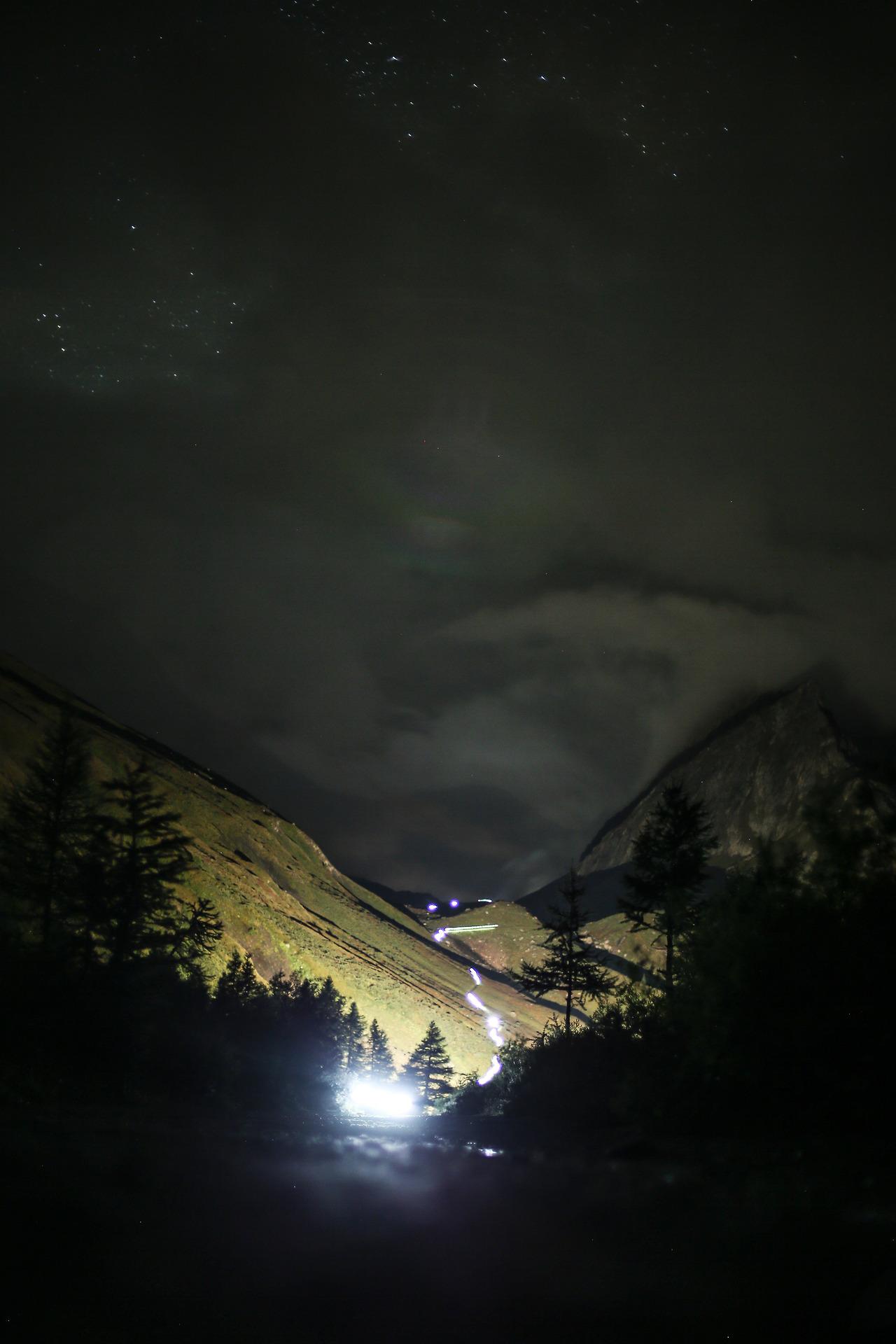 Trail de montagne nocturne, lampes frontales sinuent dans la nuit